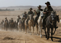 Descendants of soldiers from the Australian and New Zealand Army Corps (ANZAC), ride horses along th