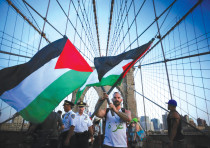 A MAN holds two  ags as demonstrators at a 2014 pro-Palestinian rally march across the Brooklyn Brid