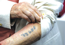 A Holocaust survivor shows the number that was tattooed on his arm in a Nazi concentration camp duri