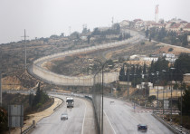 Vehicles drive on Highway 443 past the West Bank Jewish settlement of Beit Horon