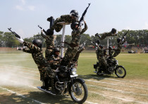 Indian policewomen perform a stunt on their motorbikes