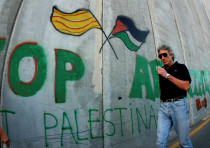 FILE PHOTO: British rock star Roger Waters walks along the Israeli barrier in Bethlehem