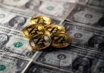 Bitcoin (virtual currency) coins placed on Dollar banknotes