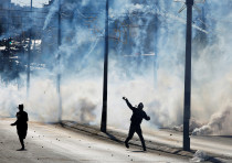 A Palestinian protester hurls stones as tear gas is fired by Israeli troops during clashes as Palest