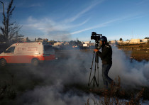 A cameraman walks amidst tear gas fired by Israeli troops during clashes with Palestinians at a prot