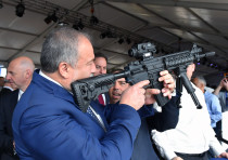 Defense Minister Avigdor Liberman holds a weapon during a visit to Sderot