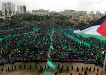 A Palestinian flag flies at a rally marking the 30th anniversary of Hamas' founding Gaza City