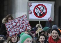 Protesters hold banners protesting the new Austrian government
