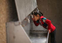 A Palestinian girl drinks from a public tap at the Jabaliya refugee camp in the Gaza Strip