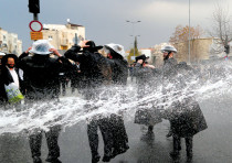 HAREDI protesters are sprayed with water by police as they block a street during a demonstration in