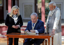 Israeli Prime Minister Benjamin Netanyahu writes a message in the visitor's book.