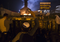 A Jewish worshipper throws candles into a fire during an annual pilgrimage to the gravesite of Rabbi
