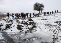 Migrants cross a snowy field, January 2016