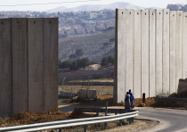 Palestinians walk near an opening in Israel's barrier in east Jerusalem