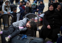 A girl sleeps as she waits with her family to cross into Egypt at the Rafah border crossing