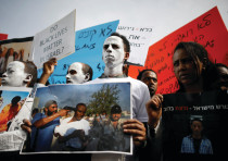 African migrants painted in white hold signs during a protest against the Israeli government's plan