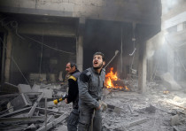 A civil defense member reacts at a damaged site after an airstrike in Eastern Ghouta