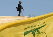 A Hezbollah member carries his weapon on top of a building on May 25, 2016.