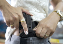 A WOMAN checks out a new pistol at a gun shop in Tel Aviv in 2015