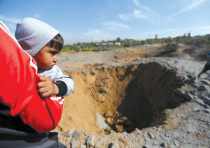 A PALESTINIAN boy is carried as he looks at the scene of an Israeli air strike, south of Gaza City,