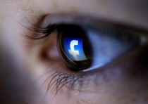 A picture illustration shows a Facebook logo reflected in a person's eye