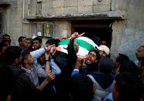 Mourners carry the body of Palestinian Faris al-Reqib, who was killed during clashes at Gaza border