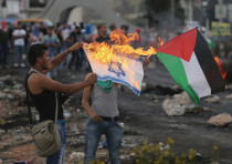 A Palestinian protester burns a replica Israeli flag as another holds a Palestinian flag