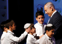 PRIME MINISTER Benjamin Netanyahu shakes hands with children during a regional development conferenc