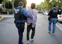 Immigration and Customs Enforcement agents escort an immigrant