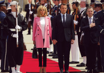 French president Emmanuel Macron and his wife, Brigitte, stand at attention for the French and US na