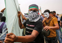 A Palestinian poses as he prepares a kite before trying to fly it with incendiaries over the border.