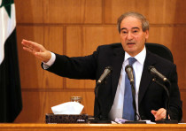 Syrian Deputy Foreign Minister Faisal Mekdad gestures during a news conference in Damascus, Syria