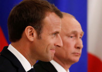 Russian President Vladimir Putin (R) and his French counterpart Emmanuel Macron attend a signing cer