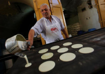 A Palestinian man makes traditional sweets ahead of the holy month of Ramadan, in the old city of He