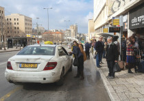 A taxi driver collects a passenger near the Jerusalem Bus Station