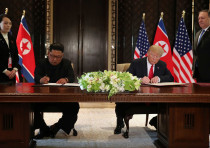 U.S. President Donald Trump and North Korea's leader Kim Jong Un sign documents that acknowledge the
