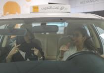 A driving instructor teaches trainee Maria al-Faraj (R) during a driving lesson