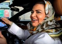 Samira al-Ghamdi, a practicing psychologist, smiles while making a stop to refuel her car as she dri