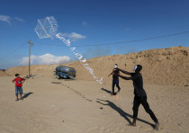Palestinians in central Gaza fly a kite loaded with flammable material to be thrown at Israel