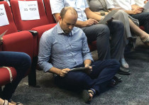 Education and Diaspora Affairs Minister Naftali Bennett sits on the floor to read the Book of Lament