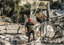A member of Hamas' military police walks through rubble at a site that was hit by Israeli air strike