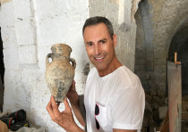 Uri Geller holds a water or oil jug that was discovered during the work in the museum.