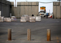 A truck parks next to a security barrier inside the Kerem Shalom border crossing terminal