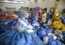 A Palestinian postal worker sifts through sacks of previously undelivered mail (August 16, 2018).