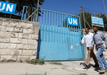 Palestinians pass by the gate of an UNRWA-run school in Nablus in the West Bank August 13, 2018
