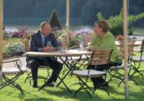 German Chancellor Angela Merkel and Russian President Vladimir Putin speak during their meeting