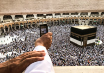 A muslim pilgrim takes a video with his mobile phone while others circle the Kaaba and pray at the G