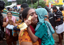 A woman cries as she holds her son after they were evacuated from a flooded area in Aluva in the sou
