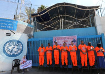 Palestinian employees of United Nations Relief and Works Agency (UNRWA) wear orange jumpsuits as the