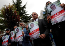 Human rights activists and friends of Saudi journalist Jamal Khashoggi hold his pictures during a pr